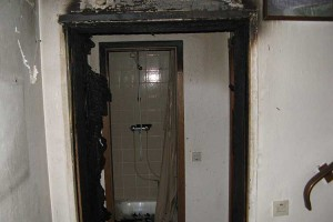 Ausgebrannte Wohnungseingangstür im Treppenaufgang...