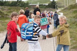 Yannick auf seinem Weg zur Dünenschule mit helfenden Händen aus der zweiten Klasse