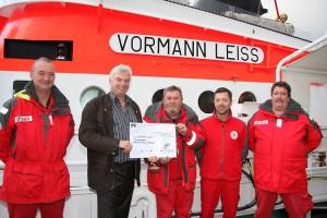 Kai Seesemann (2.v.li.)überbringt den symbolischen Scheck Jens Petersen und wachhabende Mannschaft