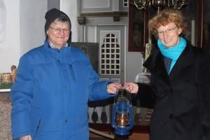Barbara Strauss übergibt symbolisch das Friedenslich an Pastorin Friederike Heinecke