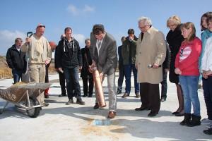 Nebels Bürgermeister Bernd Dell-Missier versenkt die Zeitkapsel in der Sohle der Sporthalle