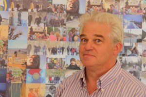 Freddie Flor, Präsident des Rotary-Clubs Amrum vor seiner selbst gestalteten Fotowand