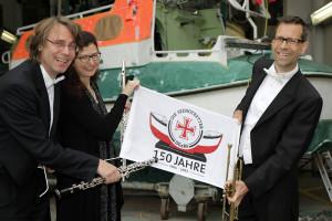 Ulrich König (Oboe), Ulrike Höfs (Querflöte) und Bernhard Ostertag (Trompete) vor der Werfthalle der Seenotretter in der Zentrale in Bremen, im Hintergrund das Tochterboot des Seenotrettungskreuzers VORMANN JANTZEN, das derzeit hier überholt wird.