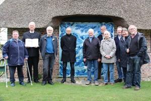 Gruppenbild vor Bibelfliese: das Team vom Öömrang Hüs mit Pastor Georg Hildebrandt und Fliesenbibel