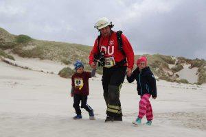 Beim Mukolauf am Strand: 10 Kameraden unter Atemschutz, Lars mit Tochter Mia und befreundetem Kind...