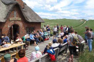 Dr. Eckhart Schrey (Mitte, stehend) begrüßt alle Gäste und bedankt sich bei den ehrenamtlichen Betreuern des Naturschutzgebiets Amrumer Odde.