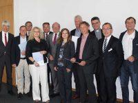 Staatssekretär Dr. Frank Nägele (links im Bild), Nordfrieslands Landrat Dieter Harrsen (Bildmitte) und Dithmarschens Landrat Dr. Jörn Klimant (2.v. rechts im Bild) beglückwünschen die 8 Wettbewerbsgewinner in Husum.